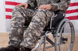Patriotic Soldier Sitting On Wheel Chair Against American Flag Financial Assistance for Veterans in Texas